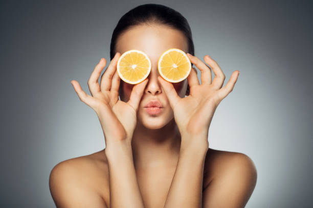 Girl with two parts of lemon Girl with two parts of lemon lemon fruit stock pictures, royalty-free photos & images