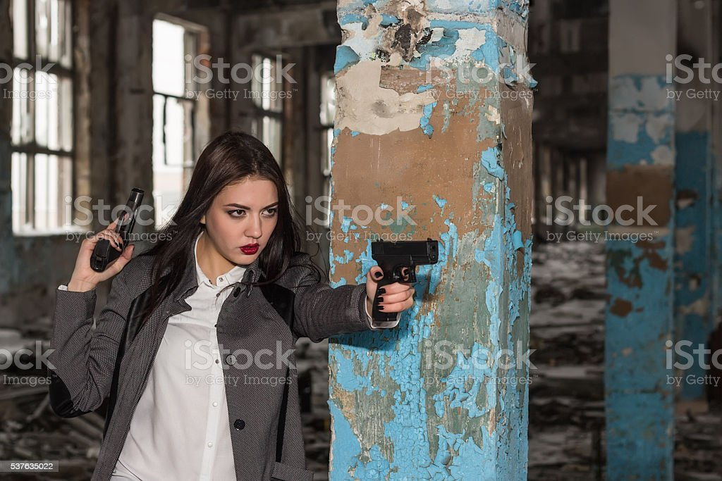 Girl with two pistols is aiming background stock photo