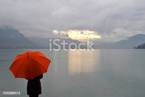 girl with umbrella meets sunrise on Lake Annecy in France