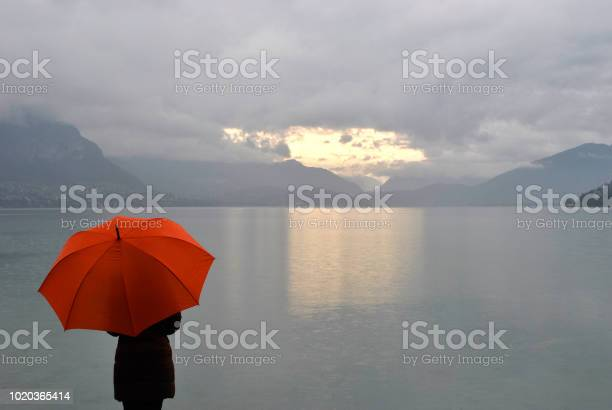 Photo of girl with umbrella meets sunrise on Lake Annecy in France