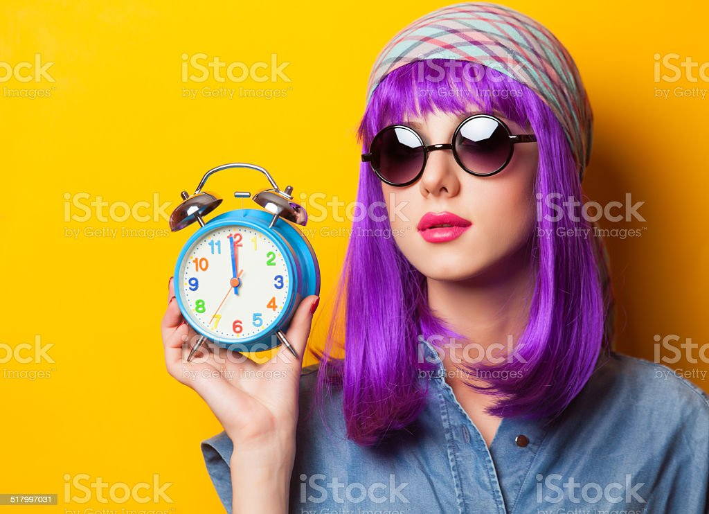 girl with violet hair in sunglasses and alarm clock stock photo