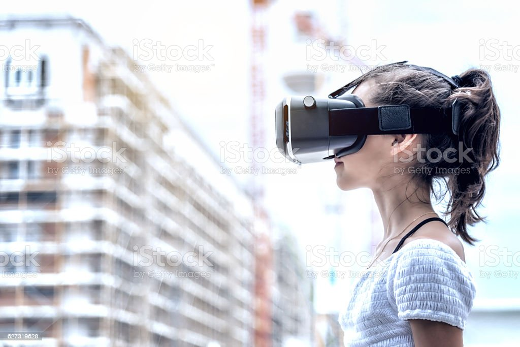girl with virtual reality simulator with blurred city background stock photo