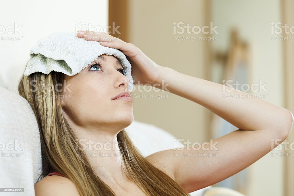 girl with wet towel on forehead stock photo