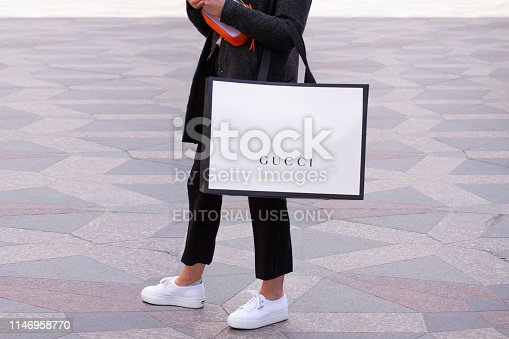 istock Girl with white sneakers standing holding a Gucci shopping bag on a street. 1146958770
