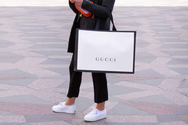 girl with white sneakers standing holding a gucci shopping bag on a street. - brand name zdjęcia i obrazy z banku zdjęć