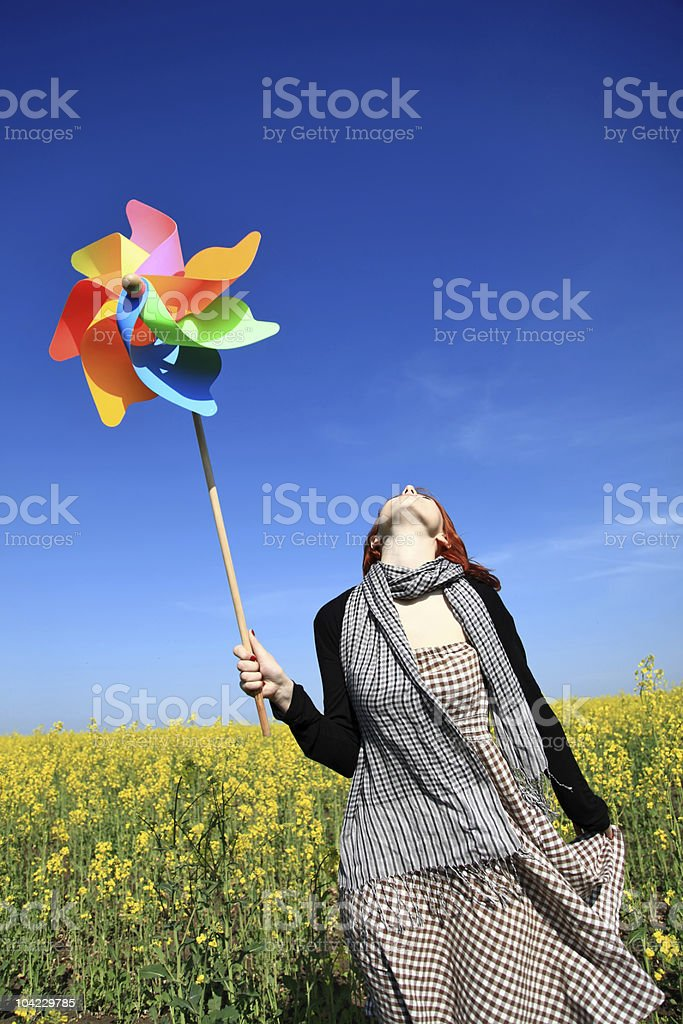 Girl with wind turbine at rape field. royalty-free stock photo