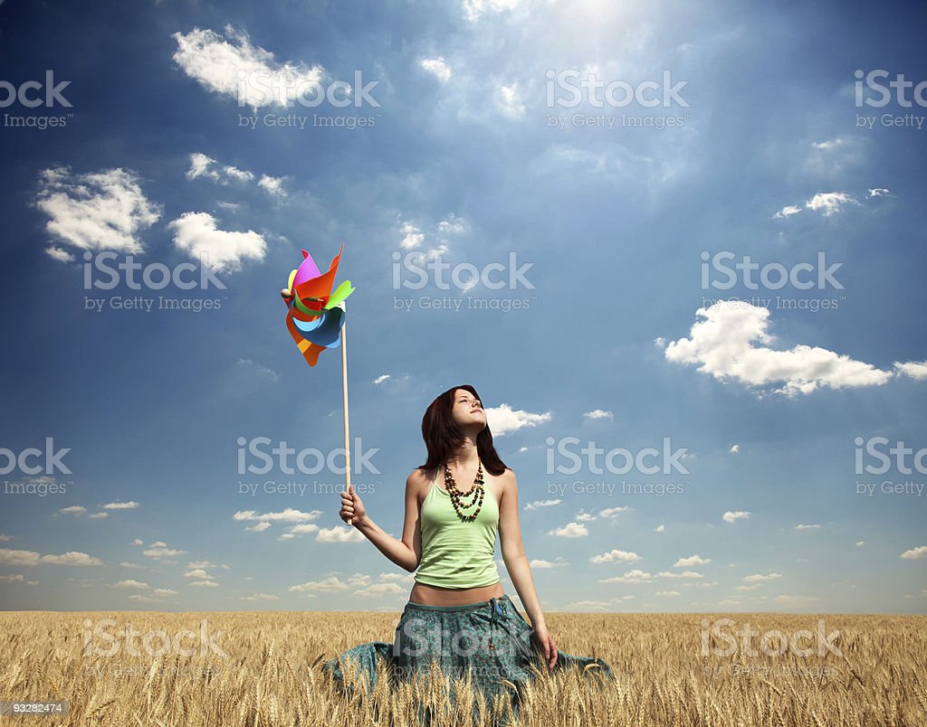Girl with wind turbine at wheat field royalty-free stock photo
