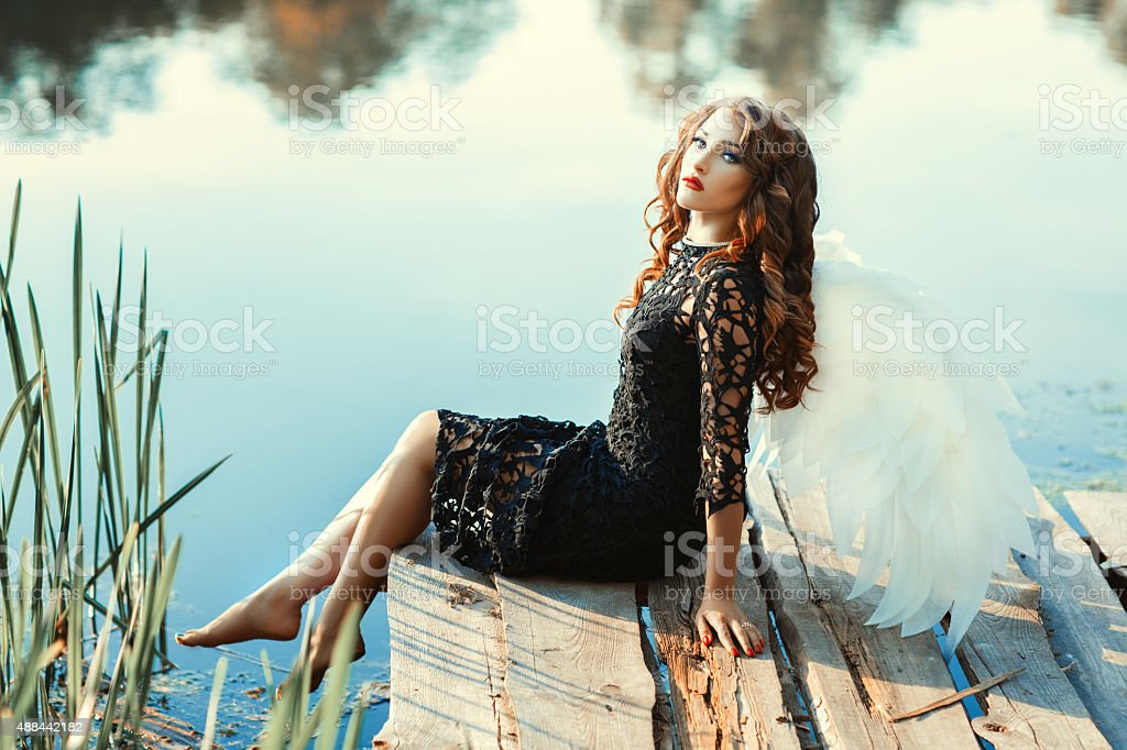 Girl with wings of an angel sitting near a river. stock photo