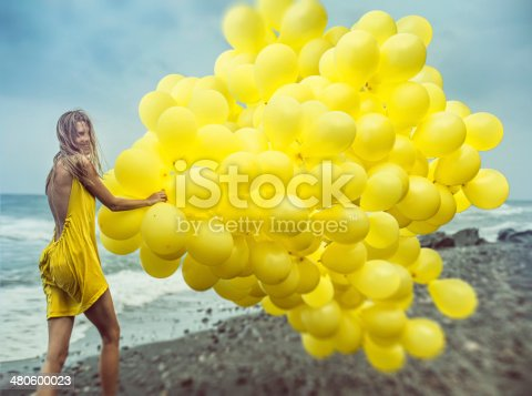 istock girl with yellow balloons 480600023