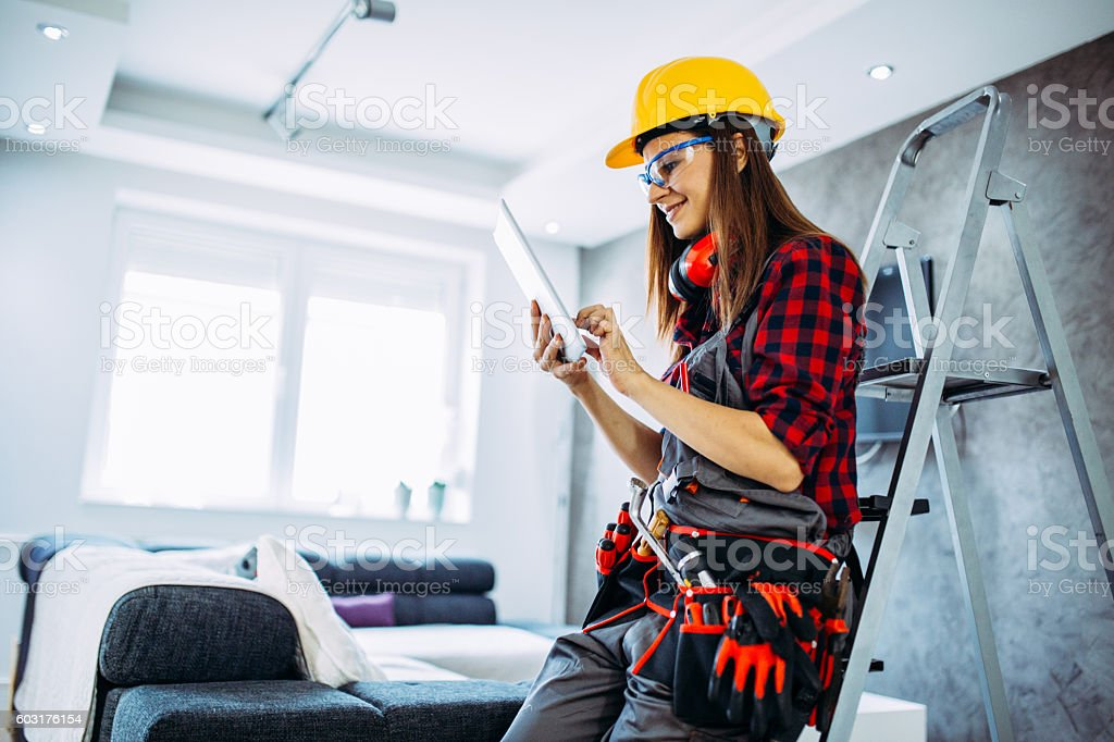 Home Improvement woman wearing hard hat and a belt full of tools, she...