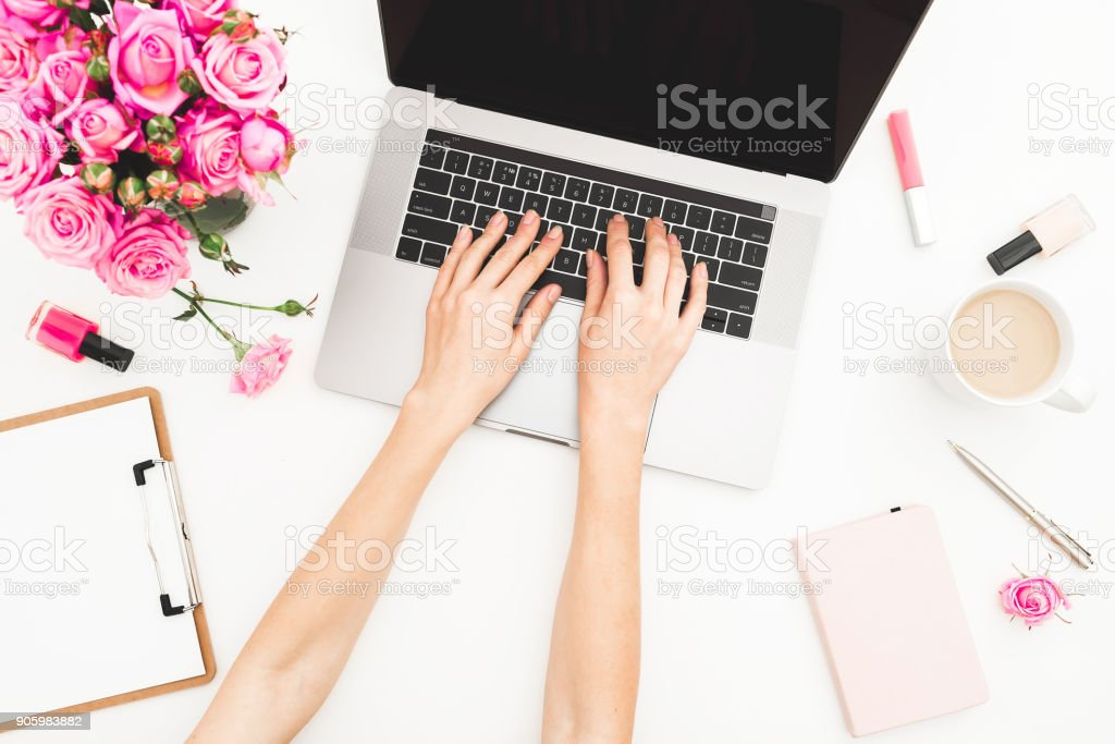 Girl working on laptop. Office workspace with female hands, laptop, pink roses bouquet, coffee mug, diary on white table. Top view. Flat lay. stock photo