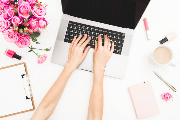 girl working on laptop. office workspace with female hands, laptop, pink roses bouquet, coffee mug, diary on white table. top view. flat lay. - femininity stock pictures, royalty-free photos & images