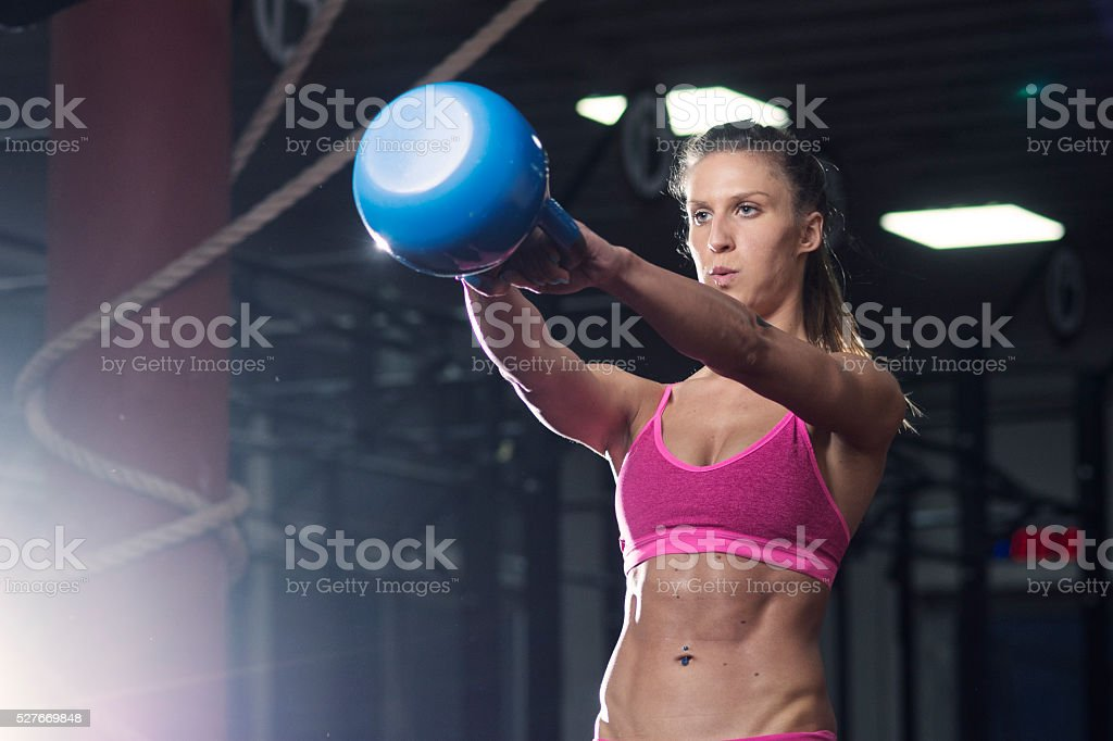 Girl working out at the gym with kettlebell stock photo