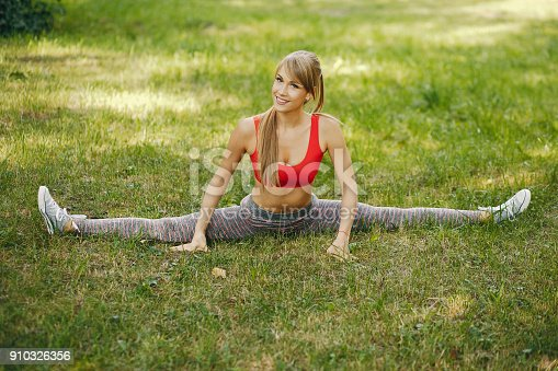 A young and sporty girl in a red top in a summer park makes a twine