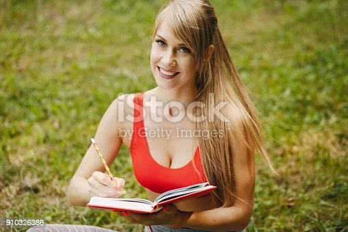 A young and sporty girl in a red top sitiing in a summer park with notebook