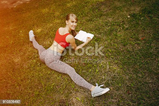 young and sporty girl in a red top in a summer park sitting in a twine and writing things in a notebook