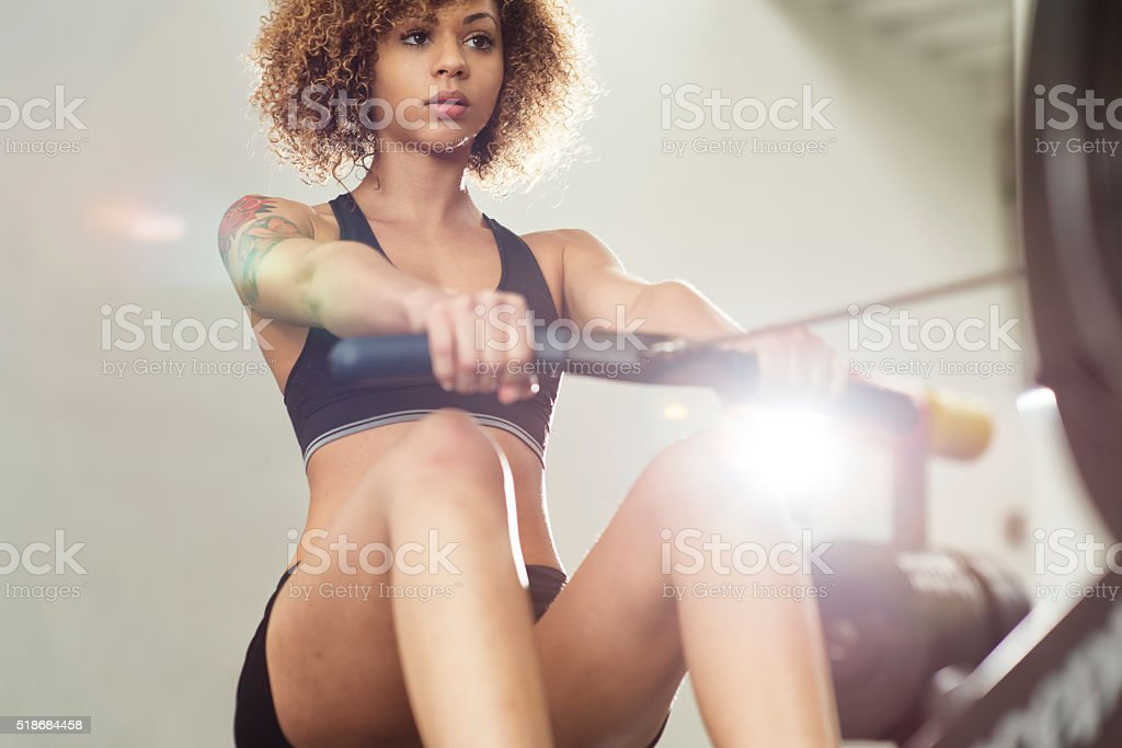 Girl working out on rowing machine stock photo