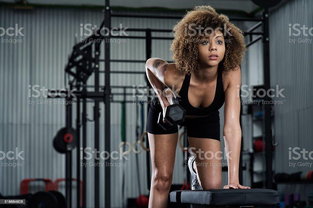 Girl working out on the bench in the gym stock photo
