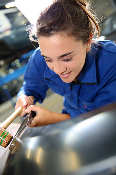 Girl working with mallet in auto shop stock photo