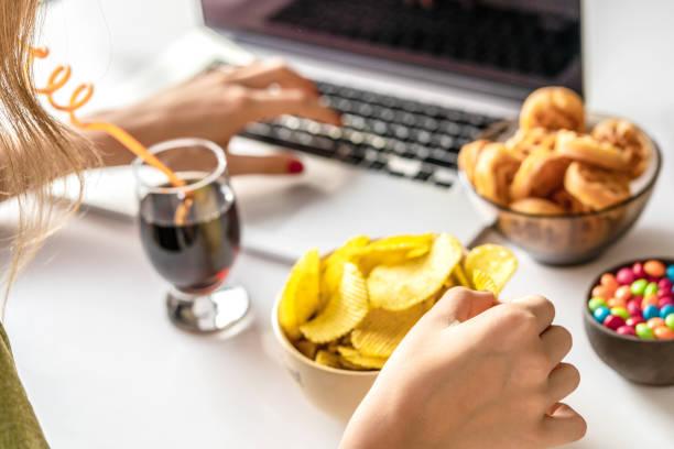 a menina trabalha em um computador e come o fast food. alimentos insalubres: batatas fritas, biscoitos, doces, waffles, cola. comida lixo, conceito. - junk food - fotografias e filmes do acervo