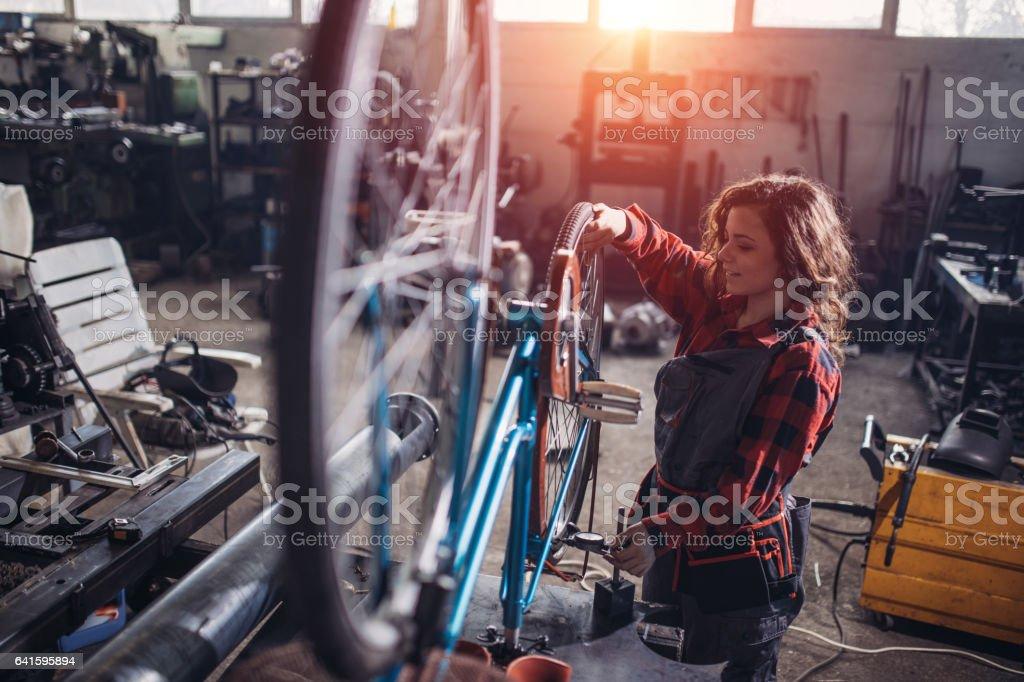 One woman, repairing her bicycle, working in workshop