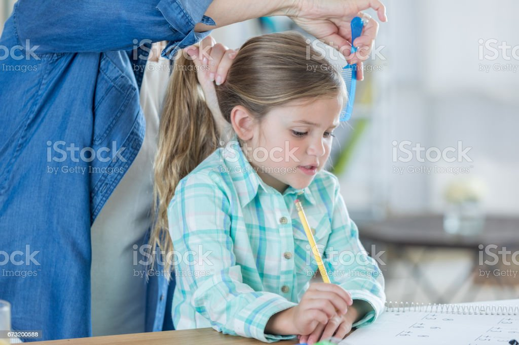 Little girl concentrates on her homework while her grandmother puts...
