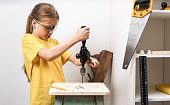A girl works with a hand drill and repairs old furniture. Education: manual labor. Portrait.