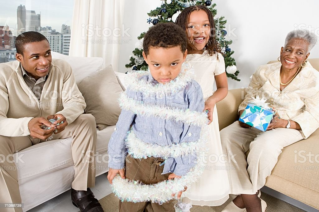 Girl wrapping brother in tinsel royalty-free stock photo
