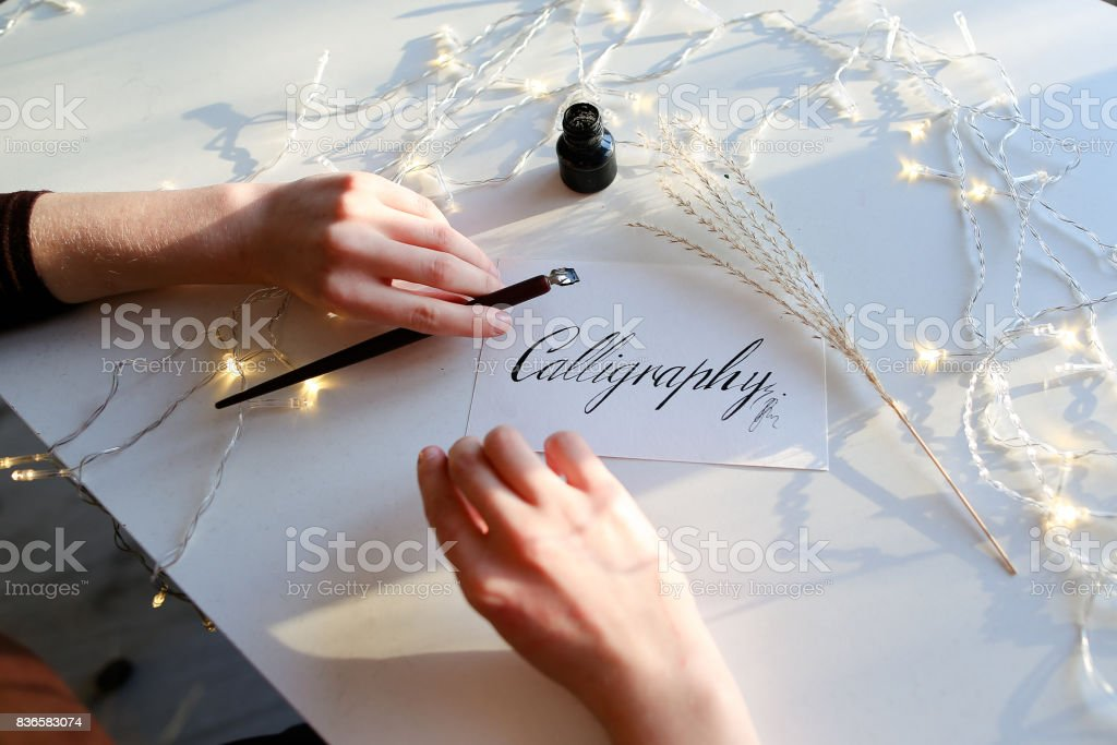 Girl writes pen fountain calligraphic letters, sitting at table stock photo