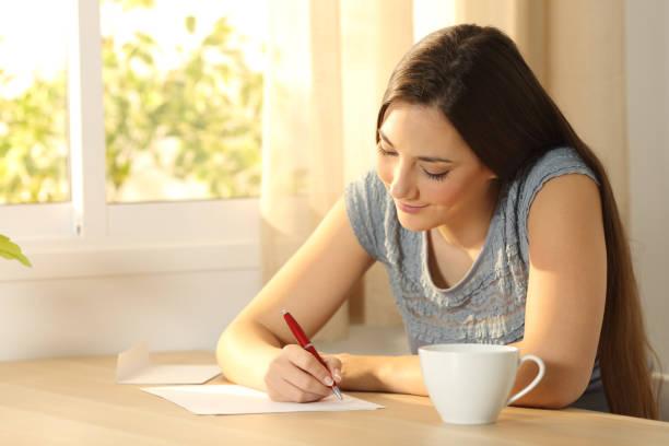 テーブルの上の手紙を書く女の子 ストックフォト