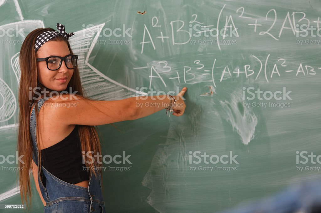 Girl writing algebra on blackboard stock photo