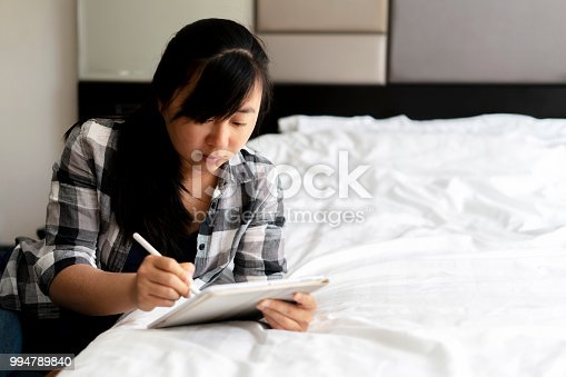 istock girl writing and drawing on digital tablet in bedroom 994789840