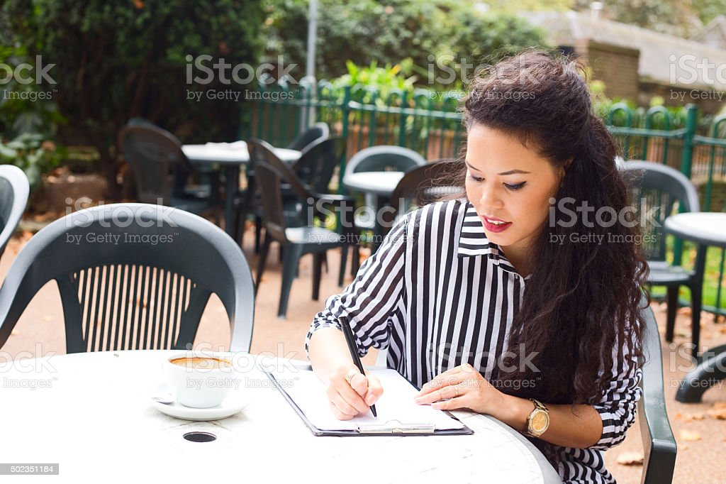 girl writing at a coffee shop stock photo