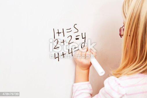 istock Girl Writing Basic Math Problems on Dry Erase Whiteboard 478479739
