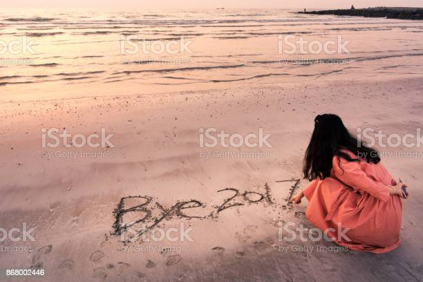 Girl writing Bye 2017 note in the sand