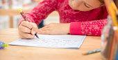 Schoolgirl writing in notebook in classroom.