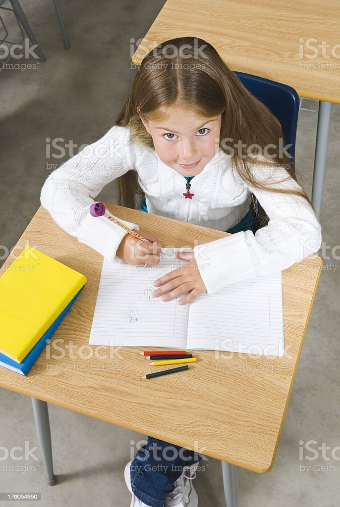 Girl writing in the classroom royalty-free stock photo