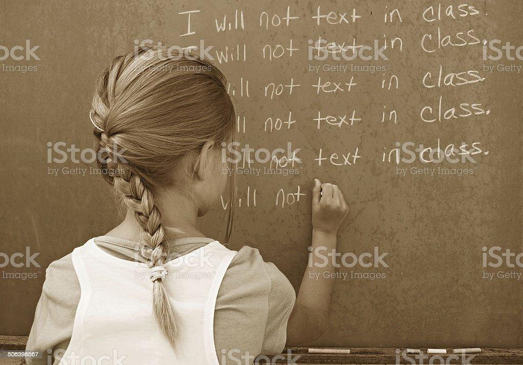 girl writing lines on chalkboard stock photo