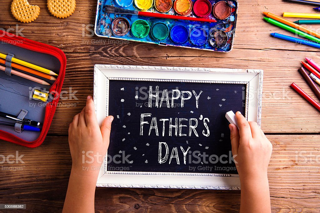 Girl writing with chalk on little board, Fathers day stock photo
