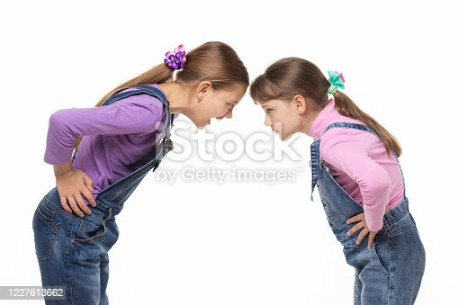 Girl yells at younger sister during altercation on white background