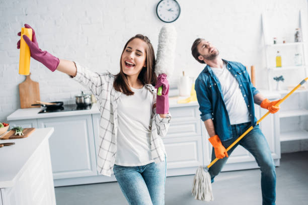 girlfriend and boyfriend in rubber gloves singing and playing mop like guitar in kitchen girlfriend and boyfriend in rubber gloves singing and playing mop like guitar in kitchen cleaning equipment stock pictures, royalty-free photos & images