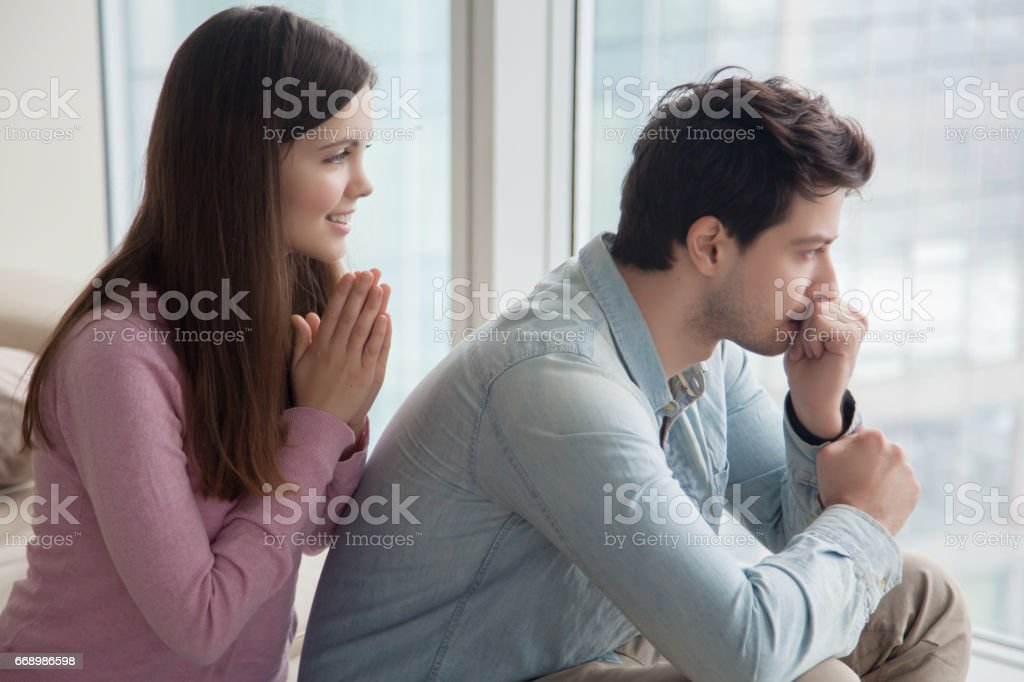 Girlfriend apologizing, asking for forgiveness serious upset boyfriend after argument stock photo