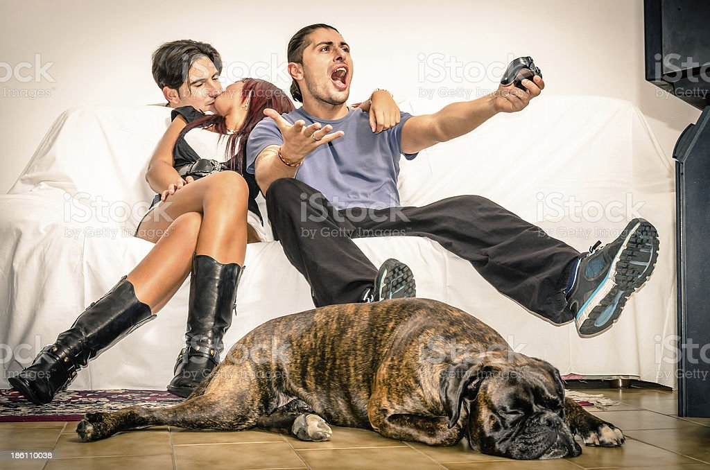 Girlfriend cheating Boyfriend while playing Videogames royalty-free stock photo