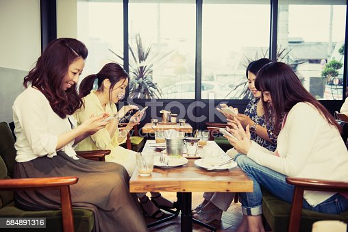 istock Girlfriend everyone using the smartphone in a cafe 584891316