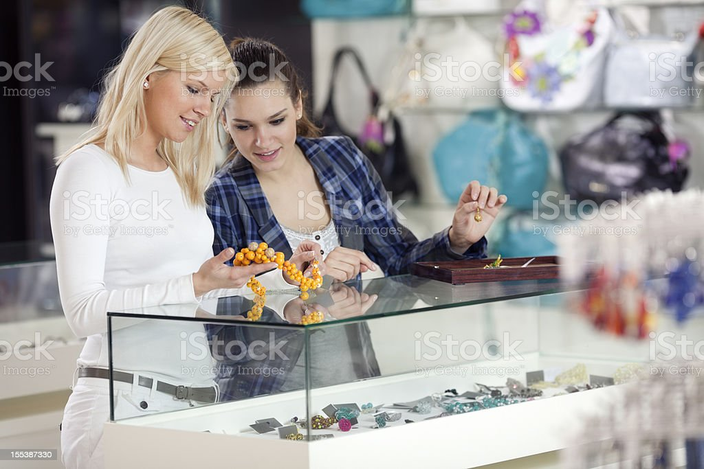girlfriends are buying fashion accessories bracelets, necklaces in departmant store stock photo
