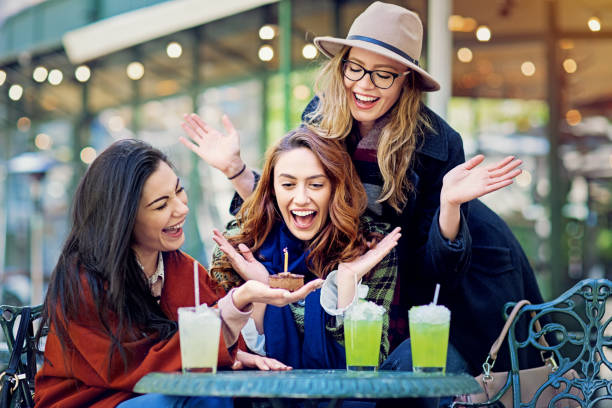 Girlfriends are celebrating birthday in a cafe stock photo