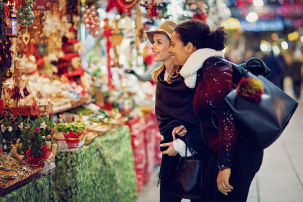 Girlfriends are choosing gifts at the christmas market stock photo