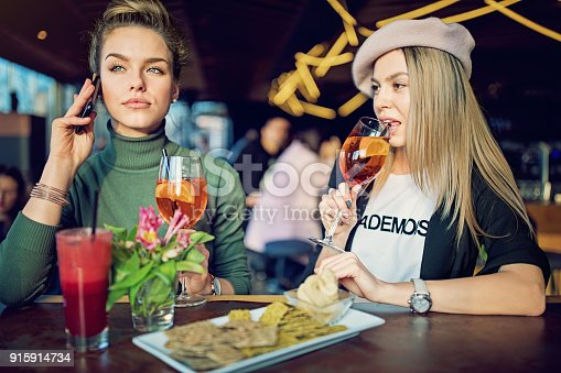 istock Girlfriends are drinking cocktails in the bar and waiting for their dates 915914734