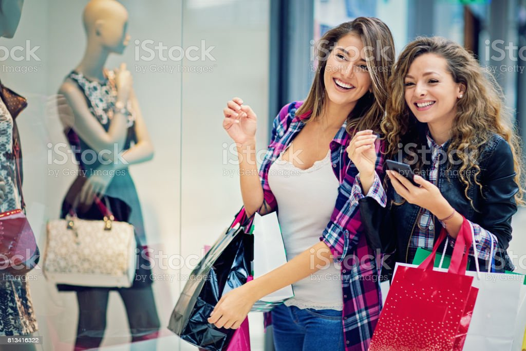 Girlfriends are looking store window in the Mall