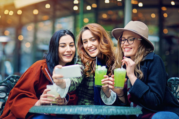 Girlfriends are taking selfie in a cafeteria stock photo